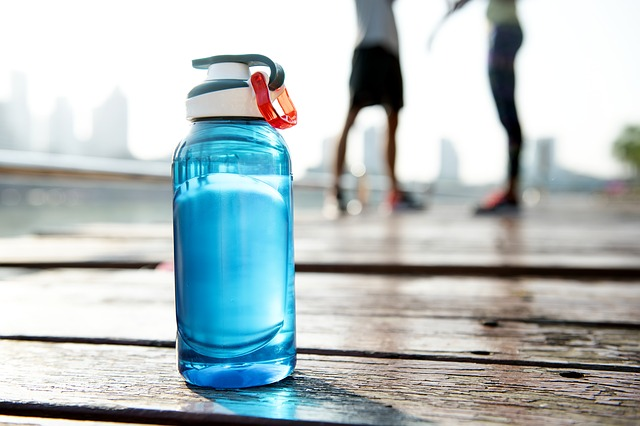 water bottle on pier in front of runners