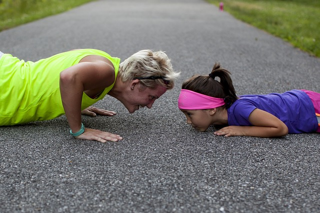 woman and young girl attempting pushups