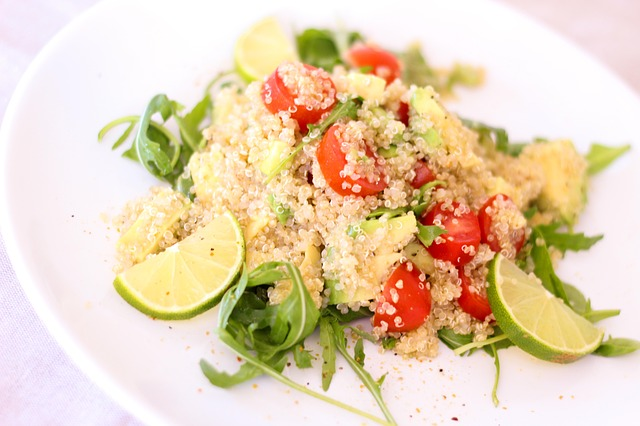 white quinoa on plate with lime tomato and arugala