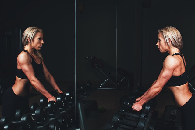 strong woman looking into mirror with dumbbells